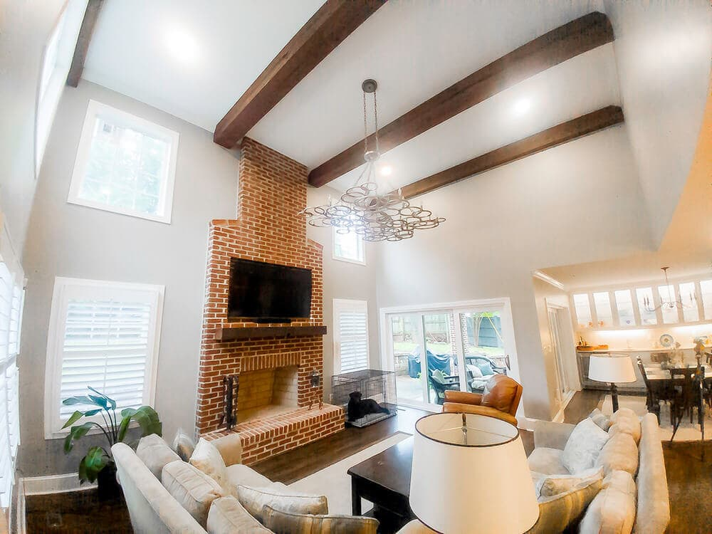 Reclaimed wood beams over fireplace in living room.