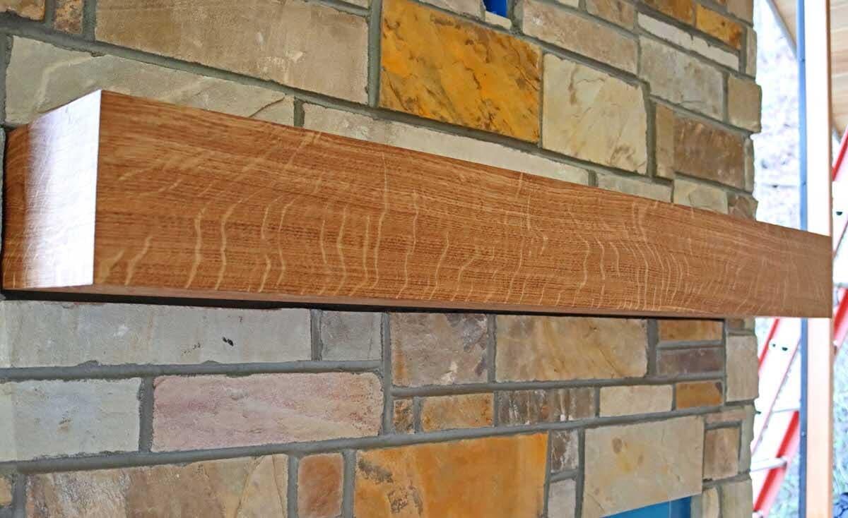 oak box mantel with wood rays against a brick Box fireplace