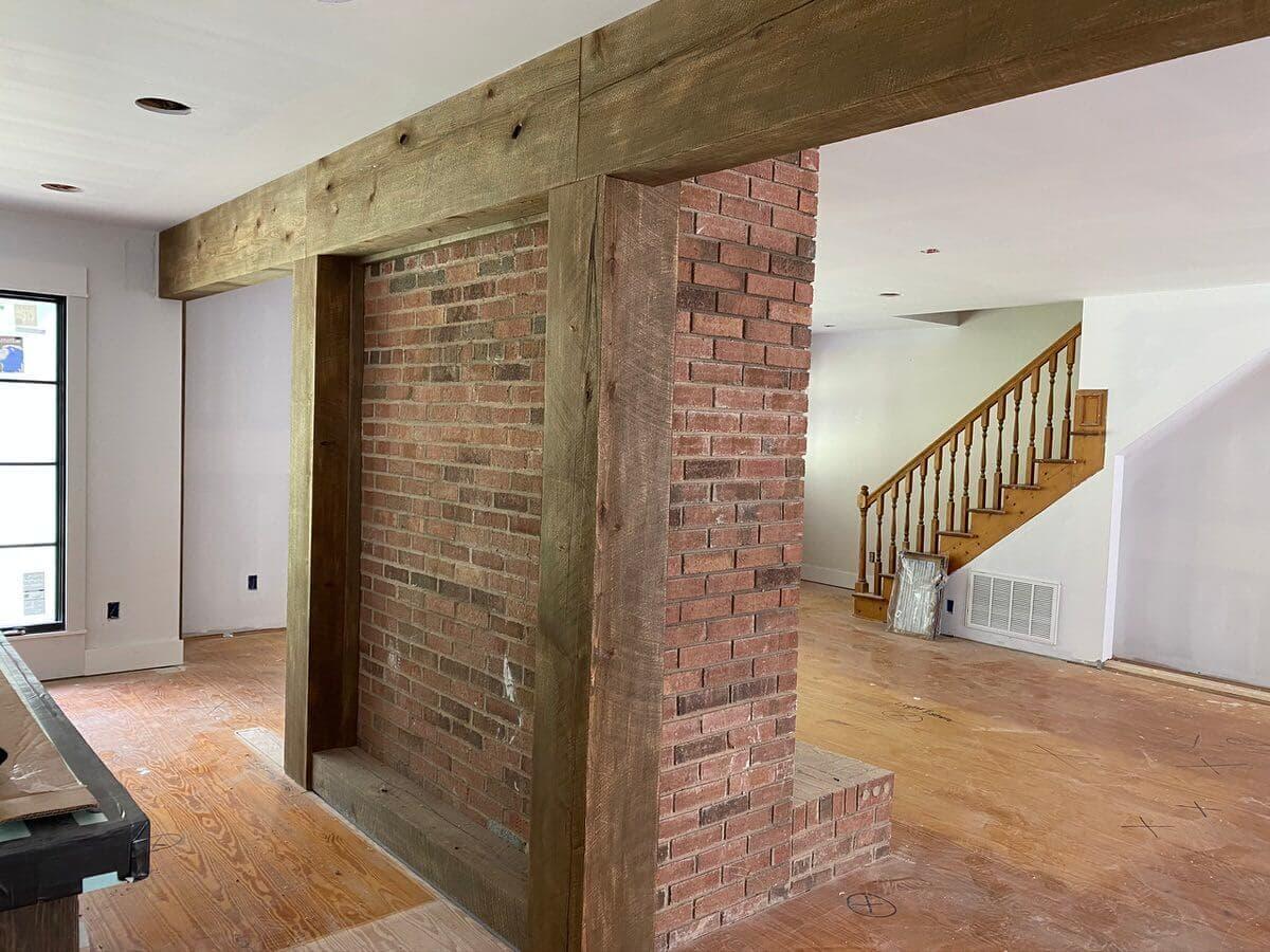 Circle sawn wood box beams surrounding brick fireplace