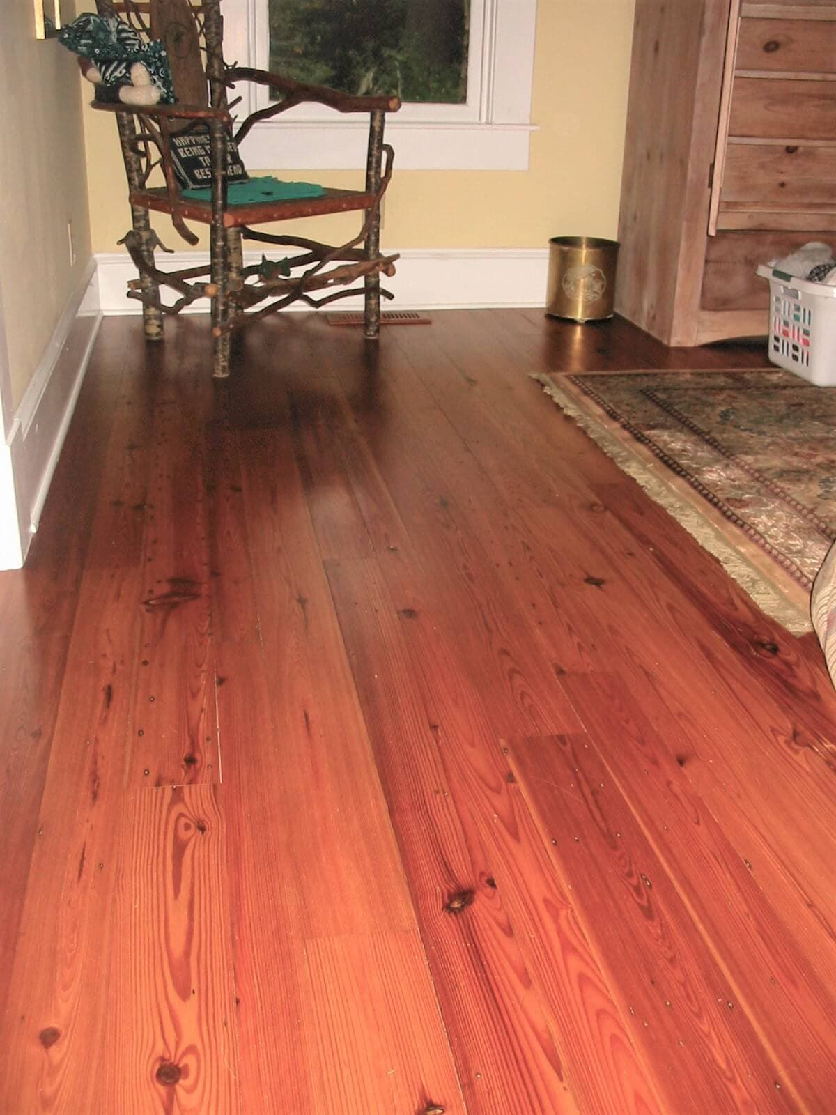 heart pine plain sawn floor near a rug and chair