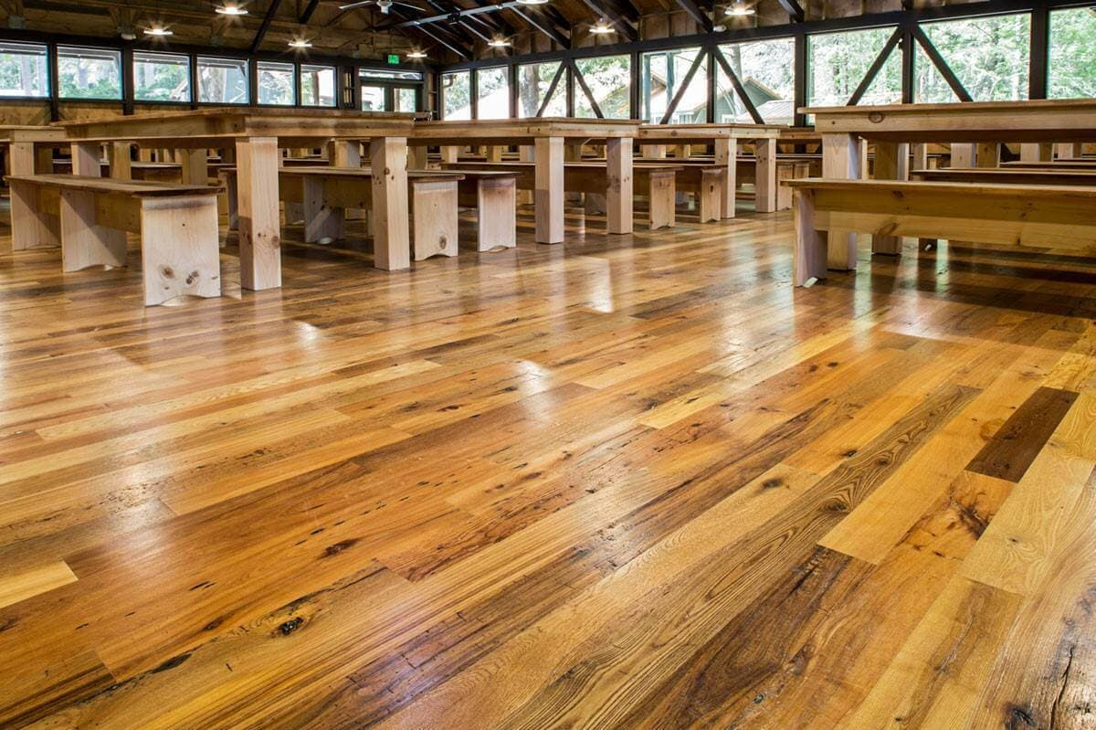 Classic smooth hardwood flooring in large rustic dining hall.