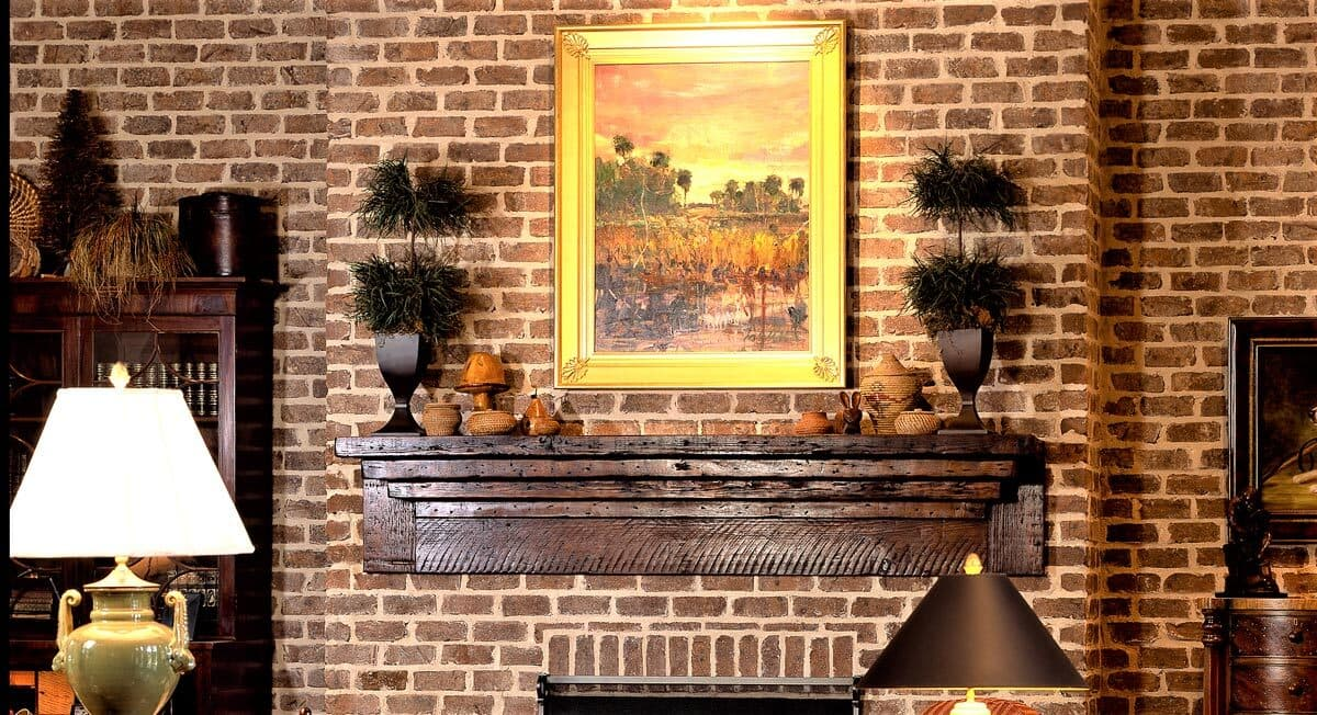 ornate custom  reclaimed wood mantel above a brick fireplace.