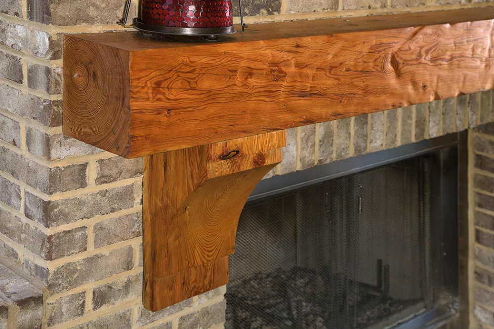 dimpled Reclaimed Heart Pine Mantel and Corbels against brick fireplace