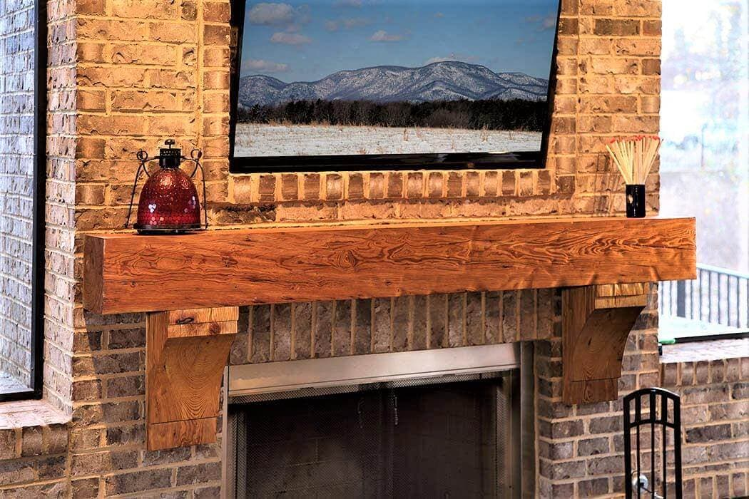 dimpled Heart Pine fireplace Mantel and Corbels under a landscape against brick