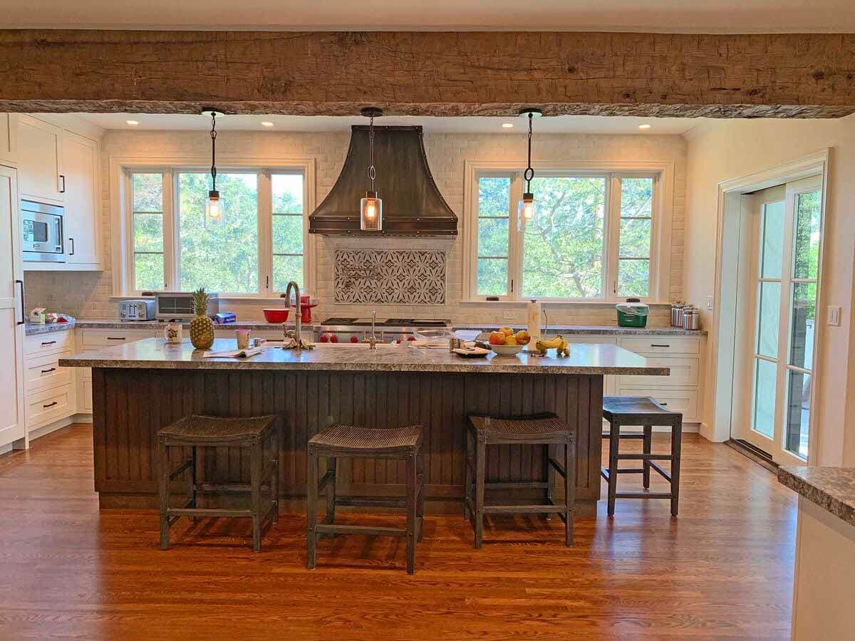 Hand hewn box beams conceal electric cords in a kitchen