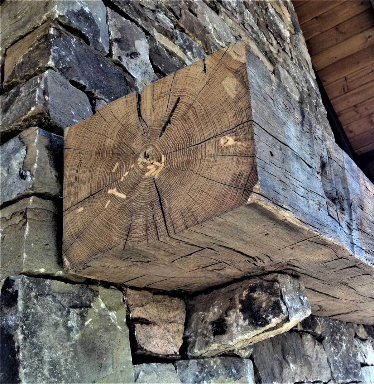 Hand hewn mantel mortise unfinished on stone fireplace.