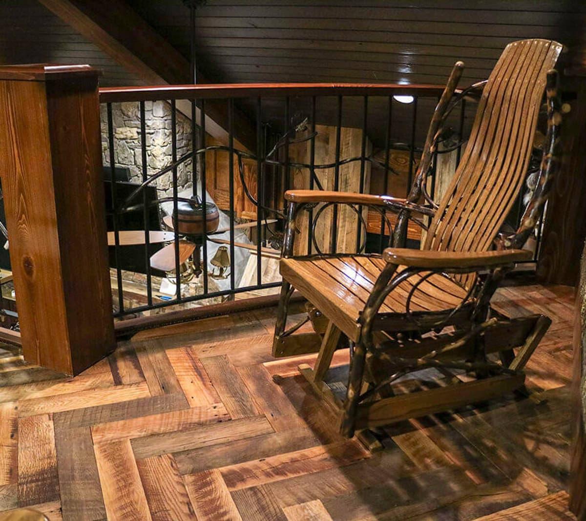 Rustic wood flooring set in herringbone pattern in mountain home loft.