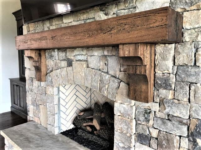 reclaimed hickory mantel and corbels over a stone fireplace