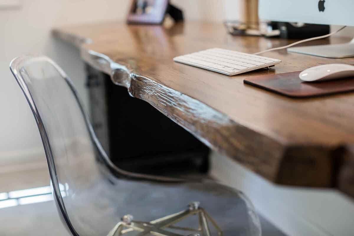 Live edge oak office table sideview closeup next to clear acrylic chair