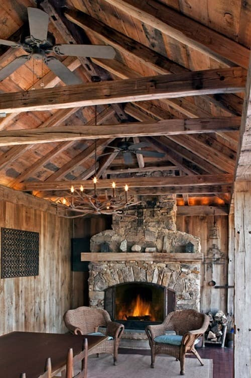 Solid reclaimed rustic wood beams define outdoor fireplace and dining area.