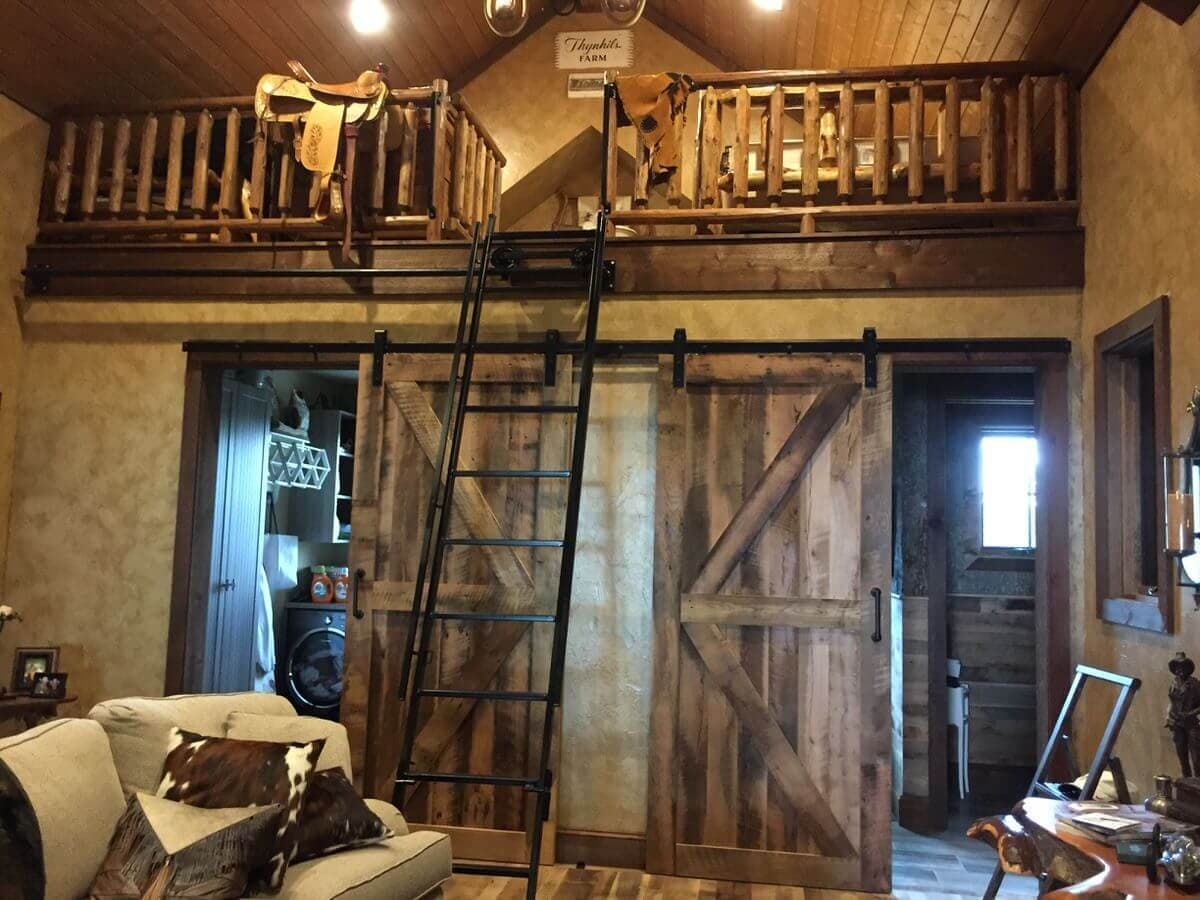 two barn doors on a sliding bar in room with a loft and cowboy details