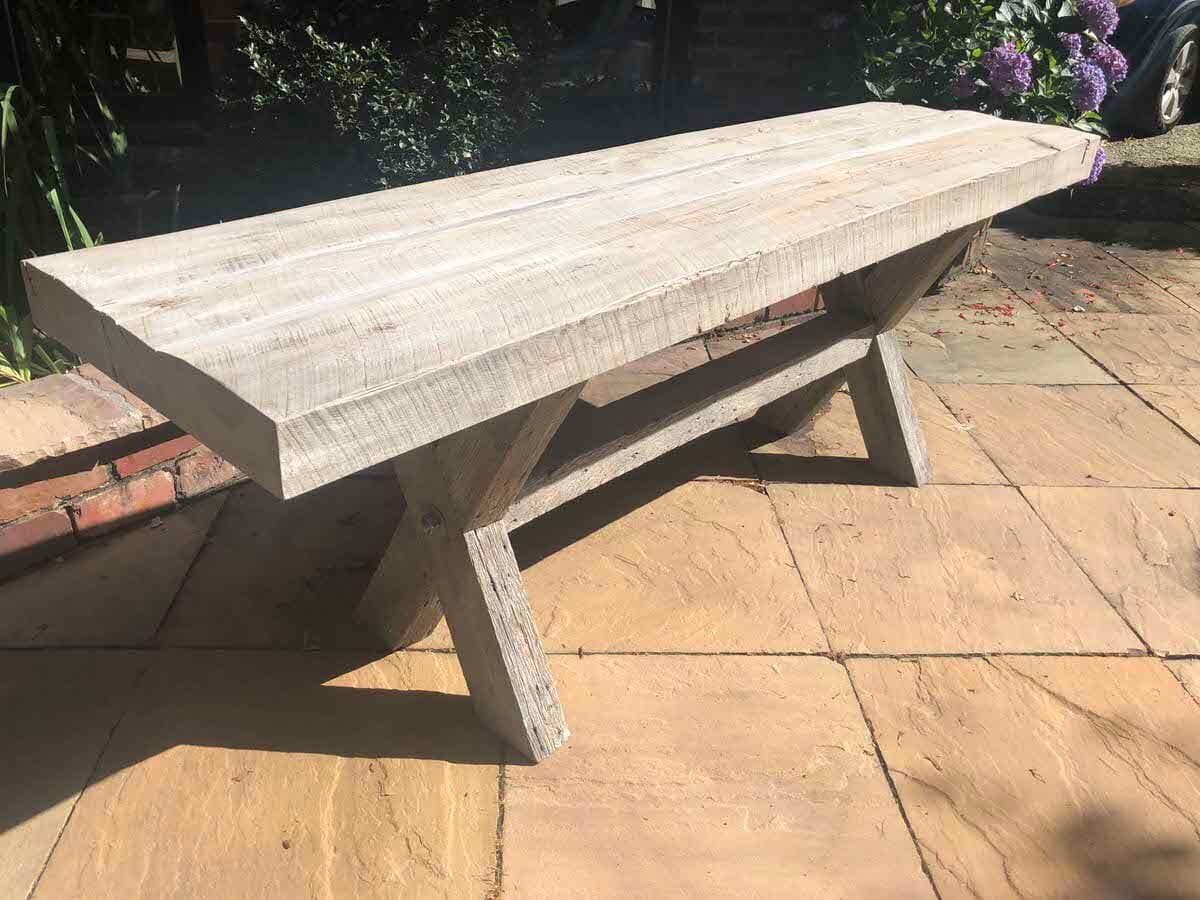 weathered gray custom reclaimed picnic table on a stone patio