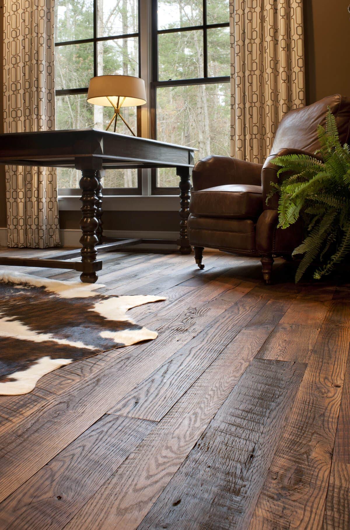 Reclaimed wood flooring with cowhide rug on top.