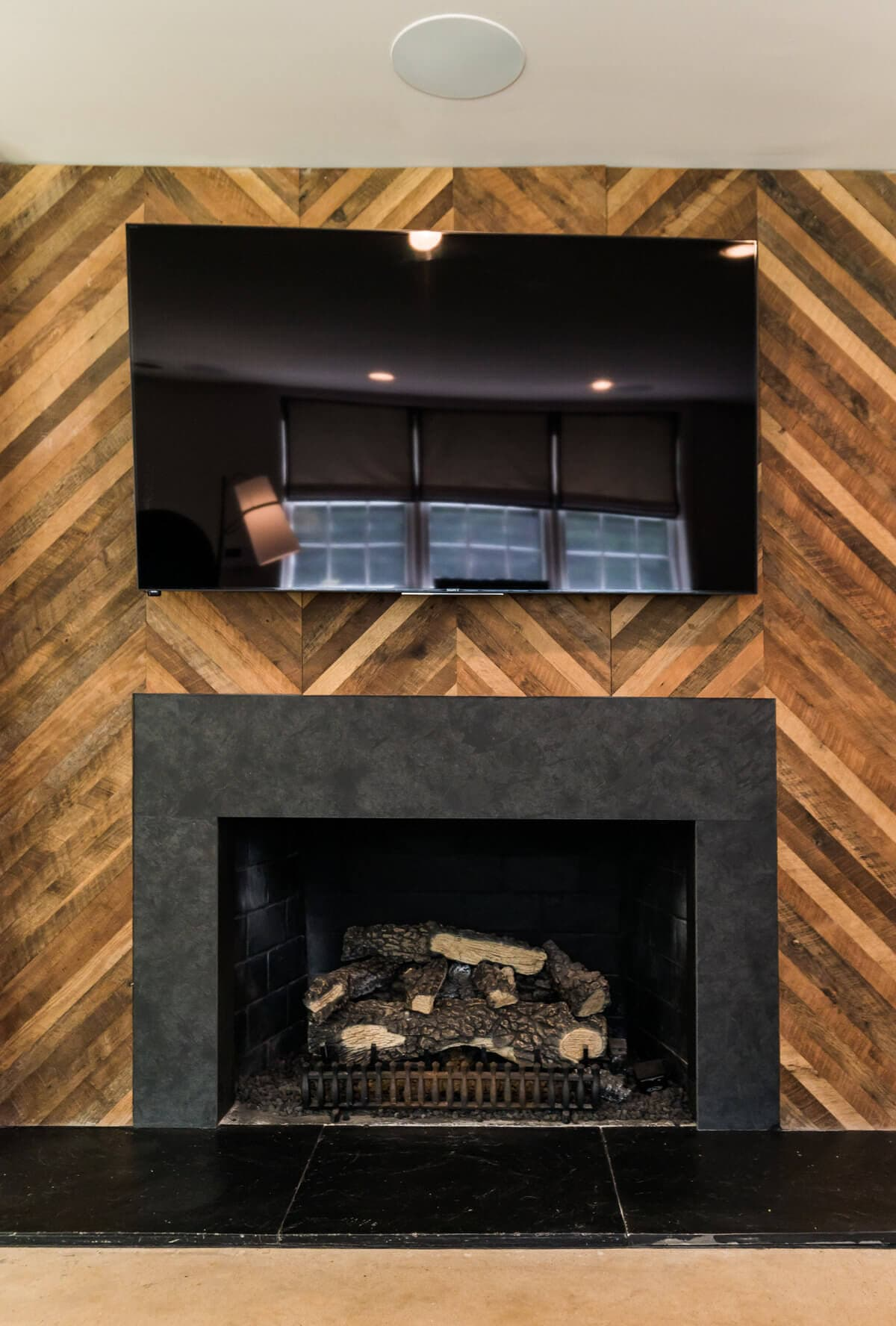 Reclaimed patterned accent wall panels around a fireplace in greenville, sc