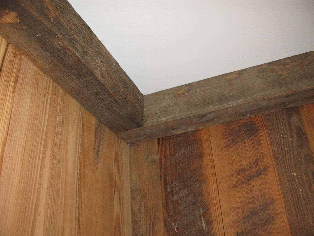 reclaimed 3 x 3 ceiling cornice beams in a corner of a reclaimed wood wall
