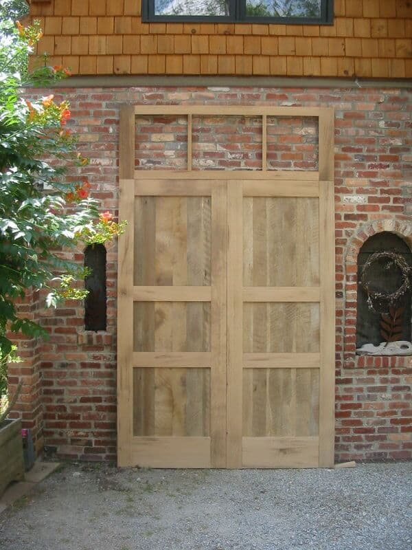 Reclaimed oak double doors with unfinished transom against a brick wall