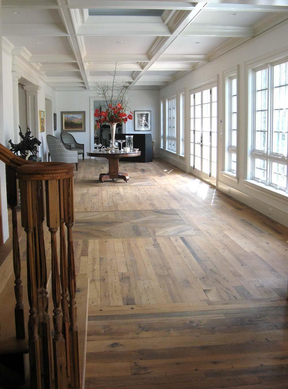 Reclaimed wood flooring in long living room with many windows.
