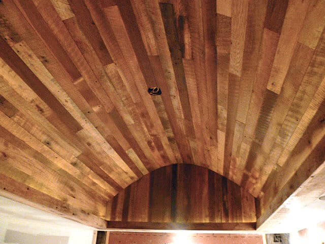 Reclaimed wood paneling on arched ceiling creates dramatic affect.