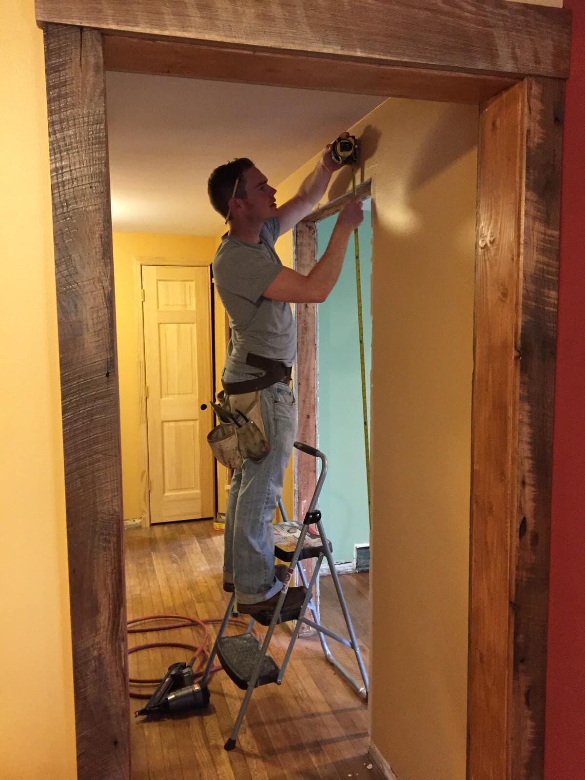 man on ladder installing Reclaimed trim around a door in asheville, nc cottage