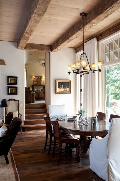 Rustic wood beam wrap above dining room.