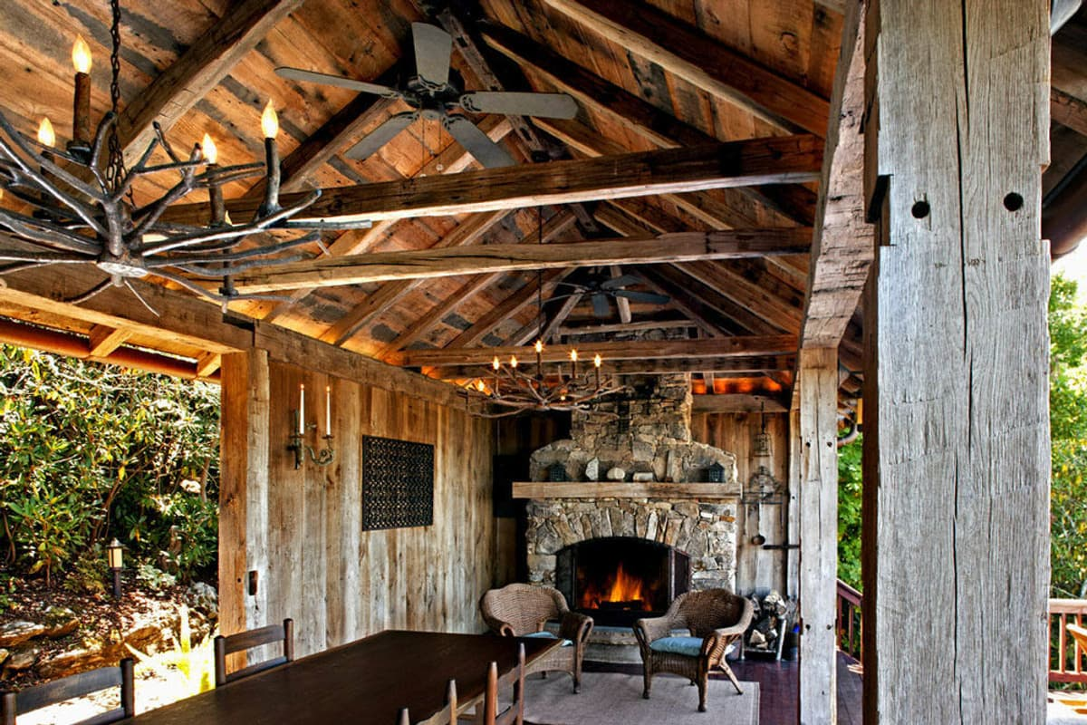 Rustic reclaimed hand hewn wood beams around outdoor fireplace and dining room.