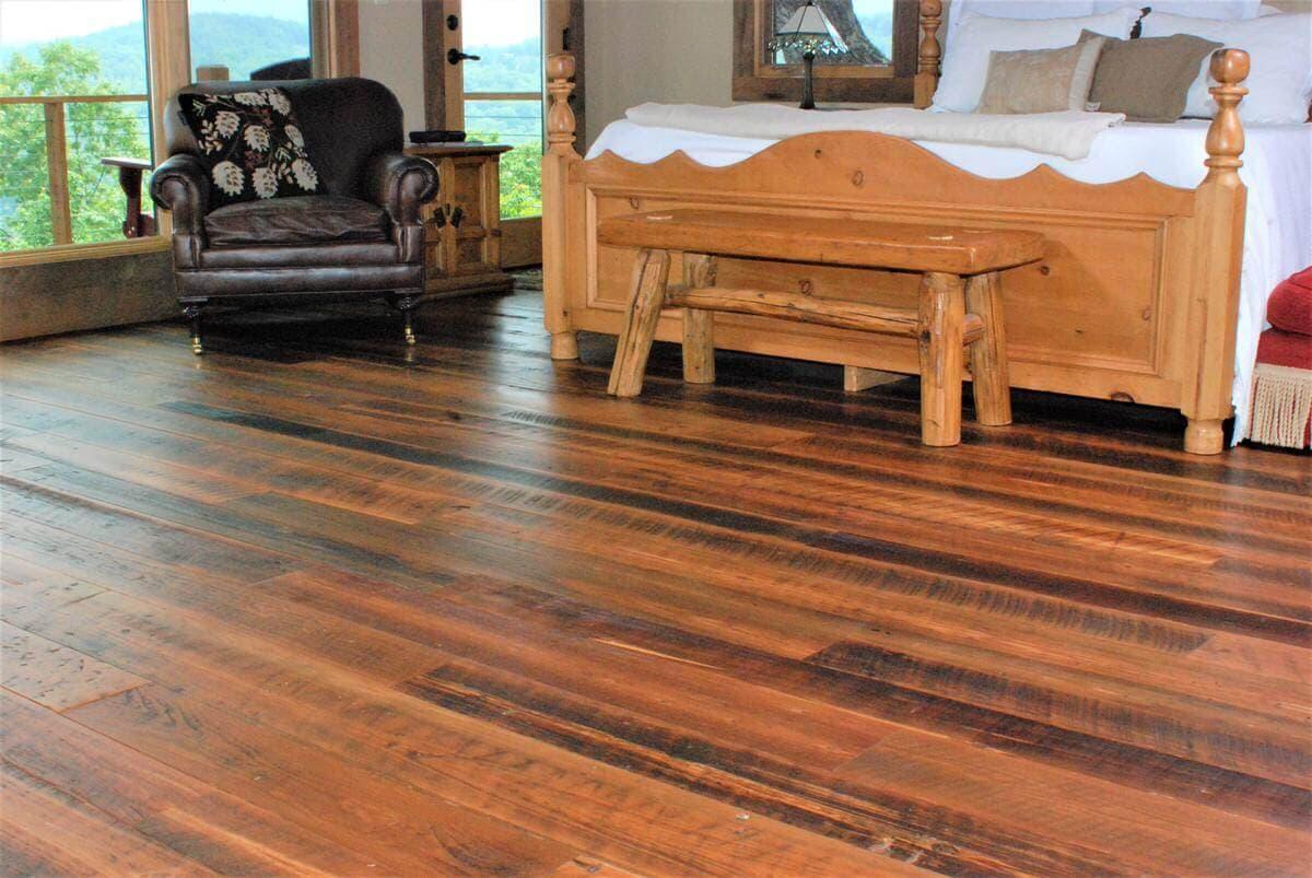 Rustic reclaimed wood flooring in master bedroom.