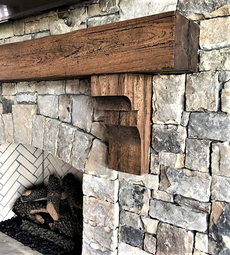 Reclaimed hickory mantel smooth planed and with corbels on stone fireplace.