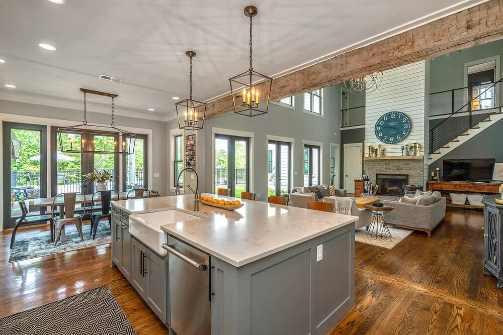 Decorative solid hand hewn wood ceiling beam separating kitchen and living room in open floor plan.
