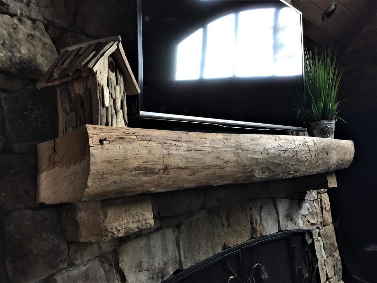 Unfinished live edge wood mantel above stone fireplace near lake toxaway nc