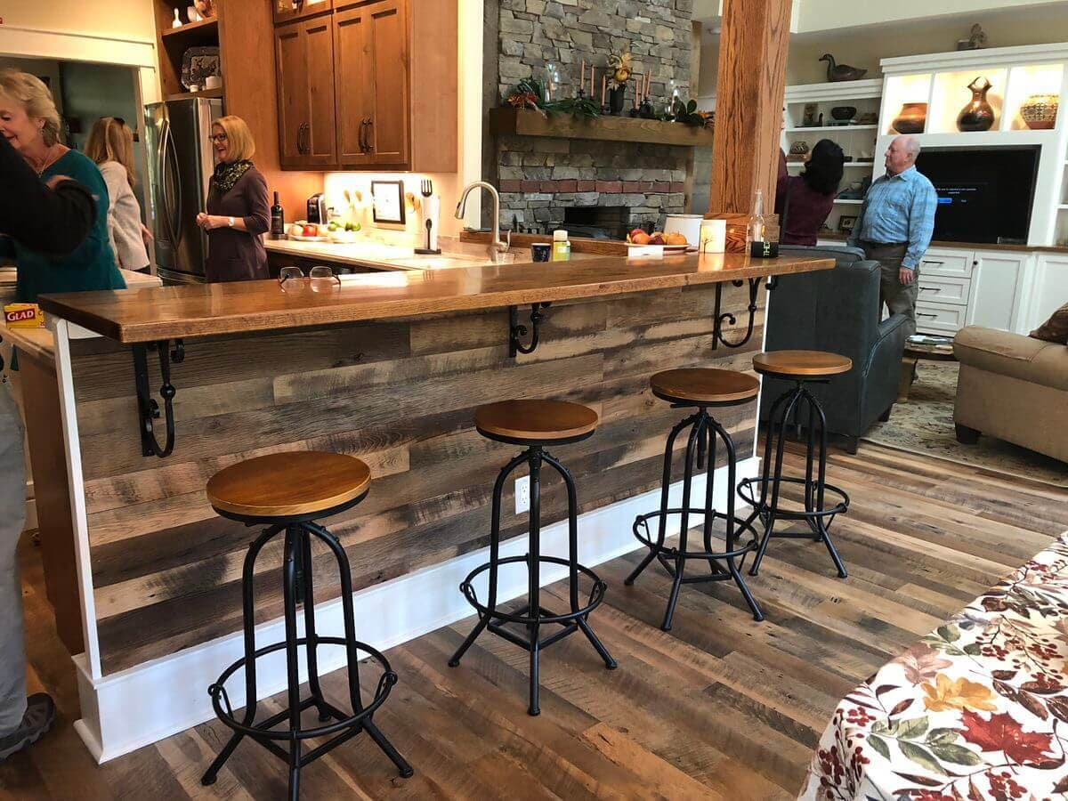 reclaimed wood side of a bar top with 4 stools in a saluda nc home