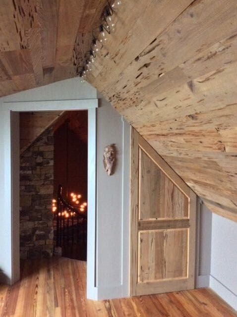 Reclaimed wood paneling for rustic wood panel ceiling accent in loft.