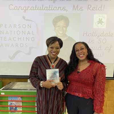 """One person holding an award that reads """"Pearson National Teaching Awards"""", standing beside another person, both are smiling."""