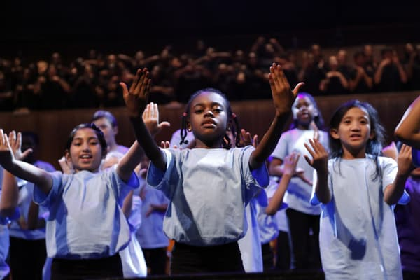 Children in light blue t-shirts singing with both arms out in front of them.
