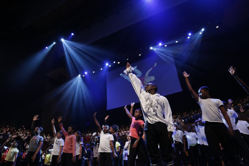 Many children singing with their right arm up on a blue-lit stage. An illustration of a man breakdancing is the backdrop.