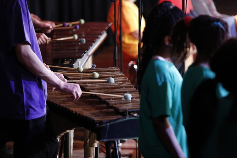 Two xylophones being played by performers wearing purple t-shirts.