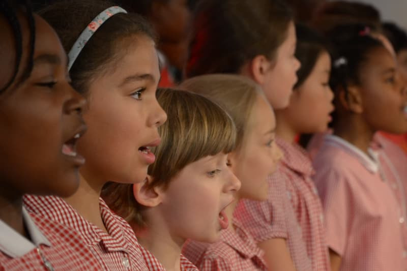 Children wearing red uniforms singing in a row.