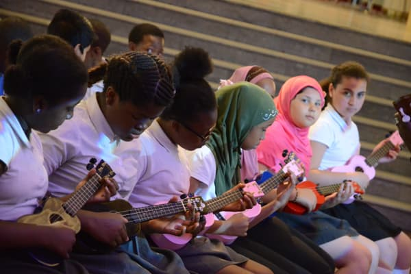 Children playing ukulele in a row.