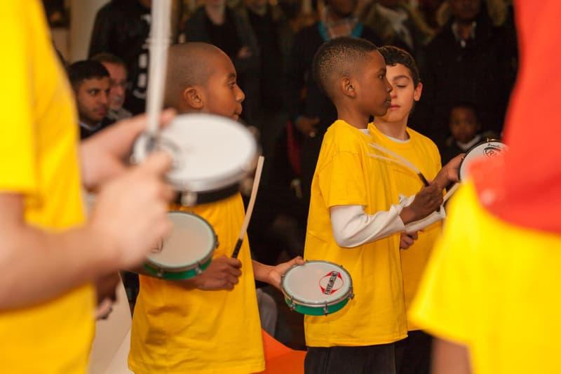 Children wearing yellow t-shirts playing tamborims.