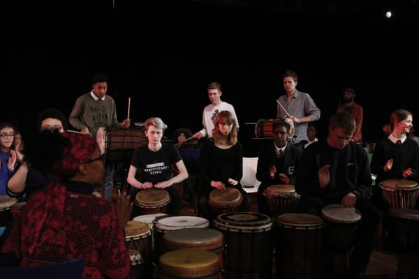 Tutor leading an African drumming group.