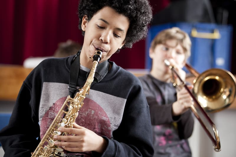 Young person playing the saxophone in front of young person playing the trombone.