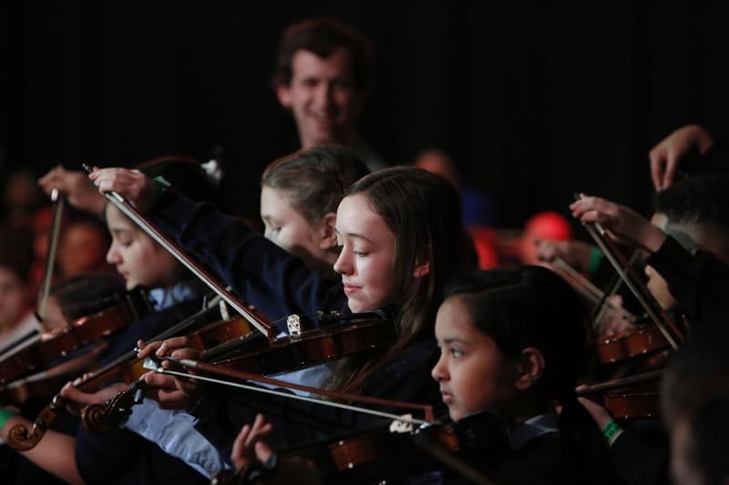 A group of young people playing violins.