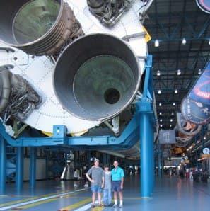 Tony standing under Saturn V booster