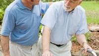 Senior man with walker and caregiver