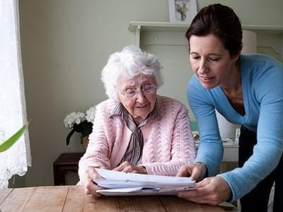 Senior woman looking at paperwork with caregiver