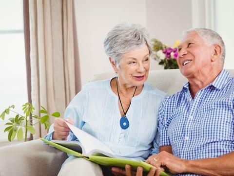 Older Couple Sitting Wearing SureSafeGO Personal Alarm