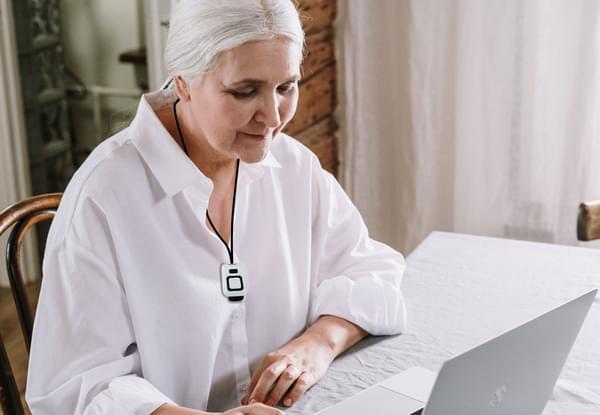 Lady Sitting Inside Wearing SureSafe Fall Alert Wearable Personal Alarm