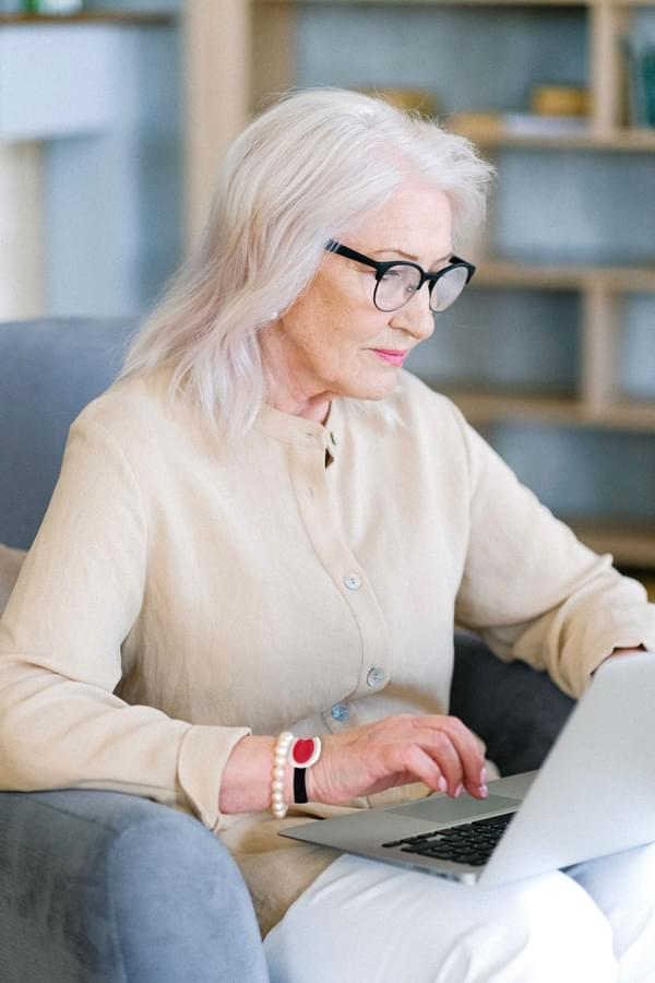 Lady Sitting Wearing SureSafe 24-7 Connect Personal Alarm