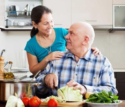 SureSafe Man Cutting Salad Woman with SureSafe 247 Pendant