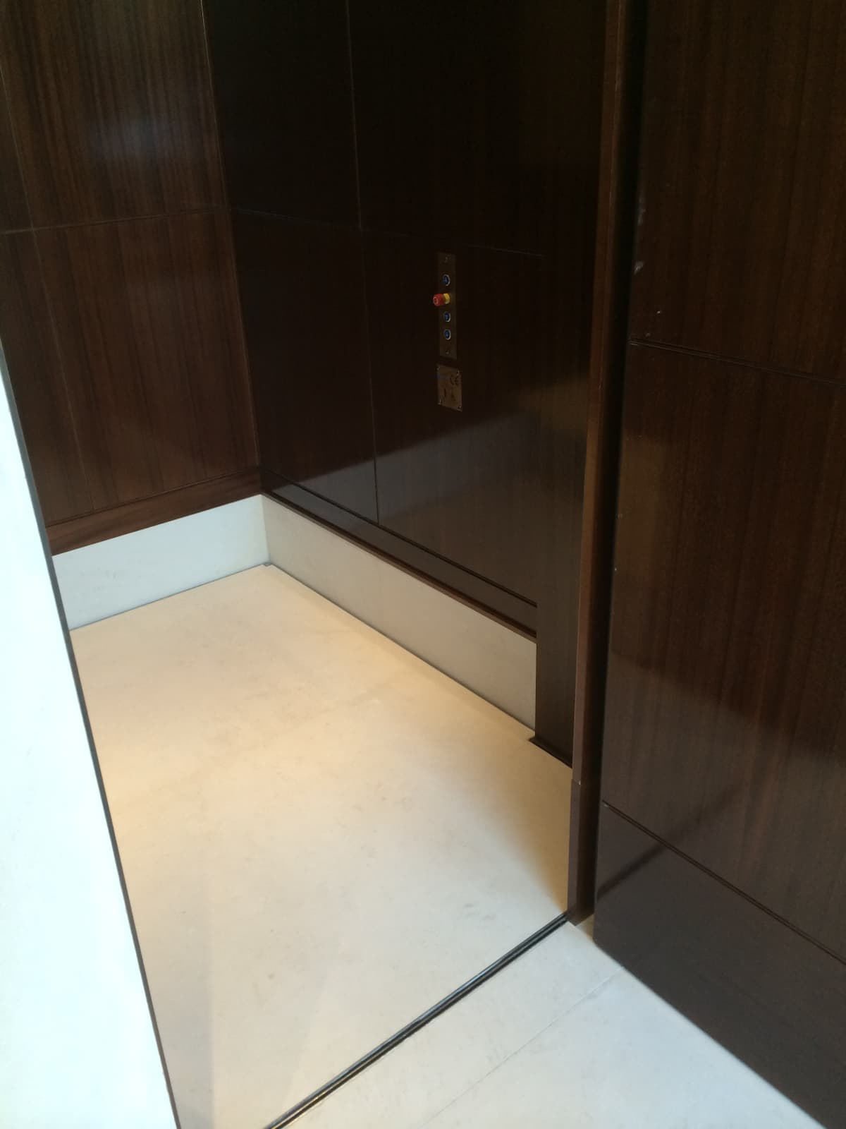 photograph of a white marble clad platform lift inside a dark wood clad lift shaft, with door open