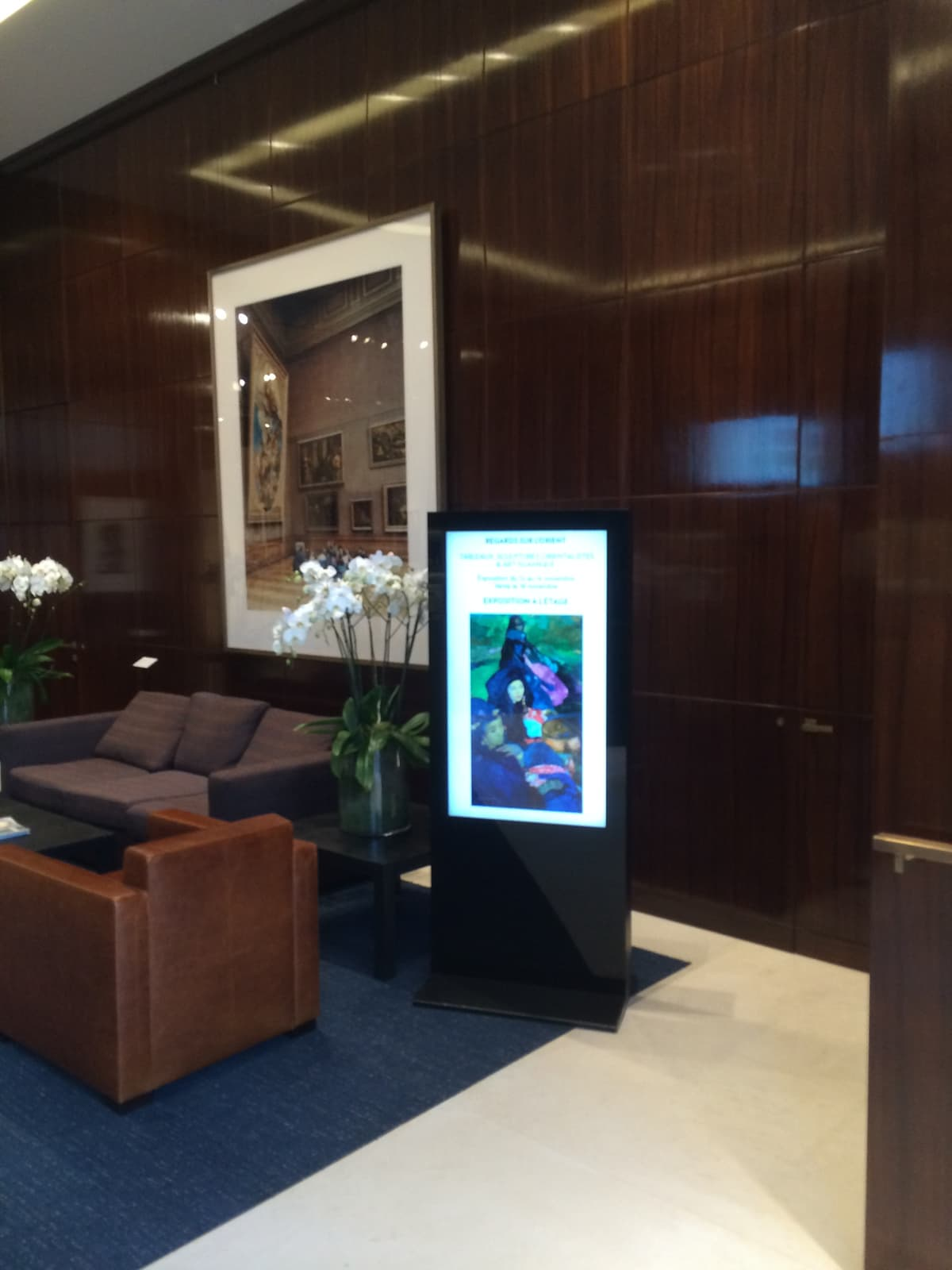 photograph of a dark wood panelled reception area with display and flowers
